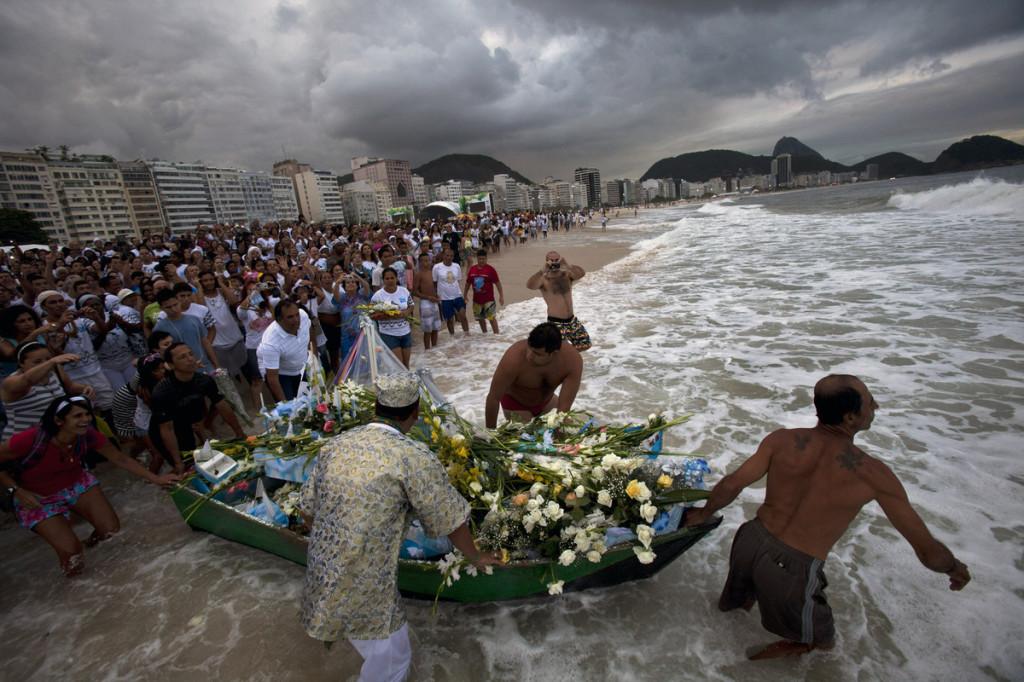 برازیلی باشندے ریوڈی جنیرو کے ایک، ایک ساحل پر جا کر سفید پھول اور تحفے سمندر کی نذر کرتے ہیں